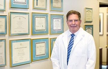 Doctor with certs in background